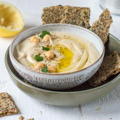 Hummus in Schale mit Kichererbsen und Knäckebrot