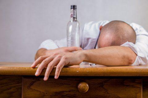 Verkatert - Alkohol - Mann mit leerer Flasche