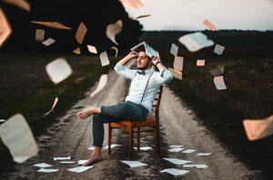 Ein barfüßiger Mann auf einem Stuhl, umzingelt von Blättern Papier