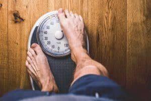 Männergesundheit ab 40 Personen Waage auf einem holzboden