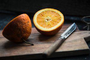 Eine zweigeteilte Orange mit Messer auf einem Brett.