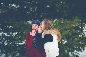Ein Mädchen flüstert einem anderen Mädchen was ins Ohr …