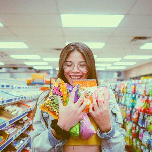 Eine Frau mit Süßigkeiten in der Hand, in einem Supermarkt.